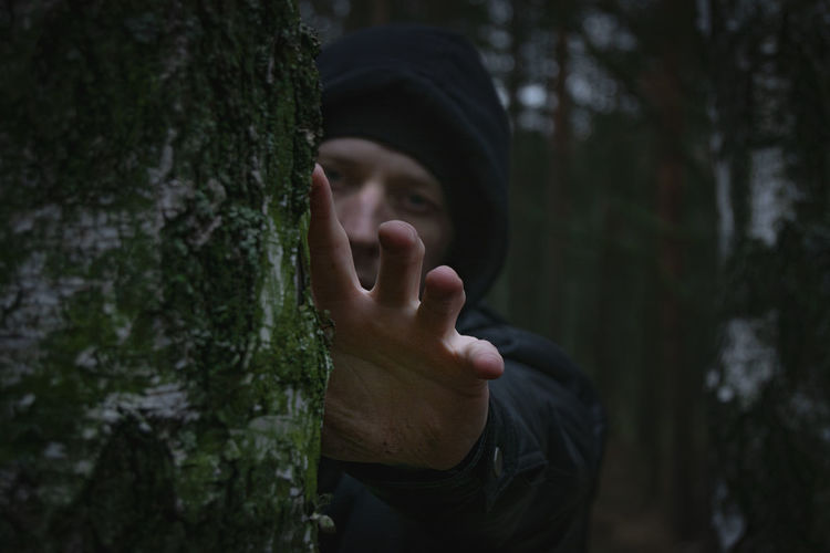 Portrait of man by tree trunk in forest