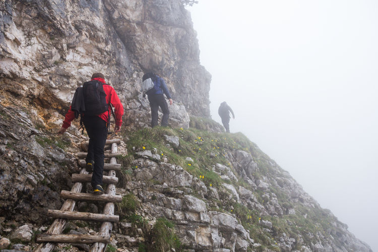 Low angle view of people hiking on mountain at triglav national park