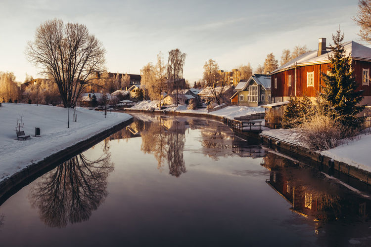 Scenic view of buildings by canal against sky during winter