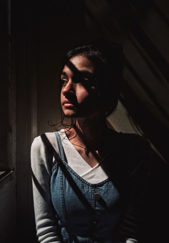 Young woman looking through window while standing against wall at home