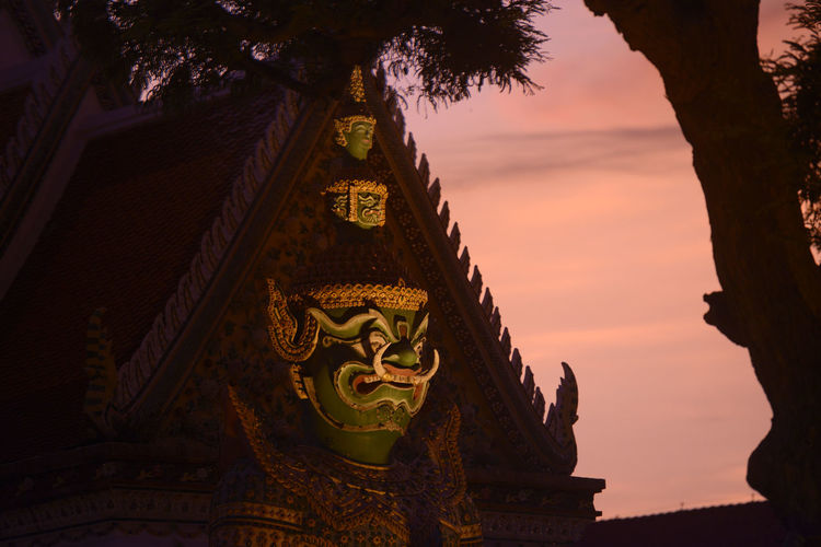 Statue of demon at wat arun temple during sunset
