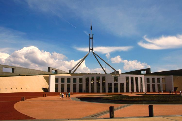 People outside parliament house against sky