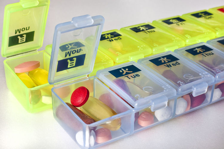 Plastic reminder pill boxes in Japanese and English, Tokyo, Japan Bored Close-up Container Medicine Picture Pills Plastic Reminder Still Life Table Vitamins