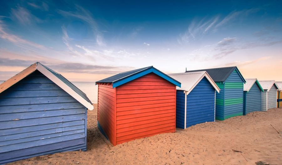 Colourful beach huts against sky and sand