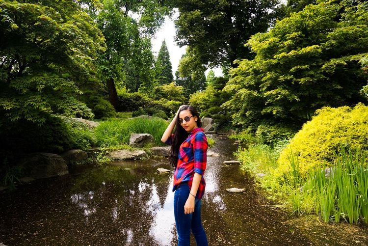 Young woman standing against stream amidst trees at park