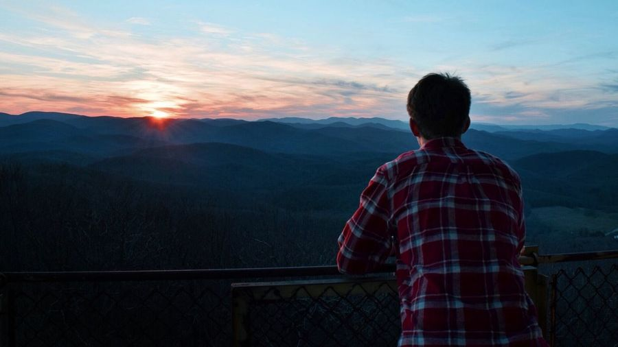 Rear view of man looking at scenery while leaning on railing during sunset