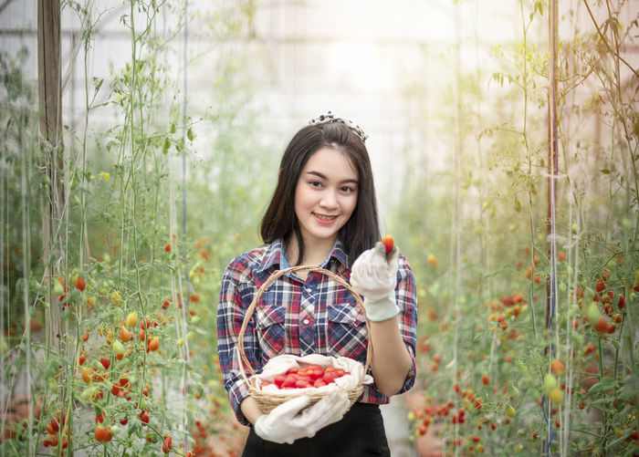 Portrait of smiling young woman holding strawberry at farm