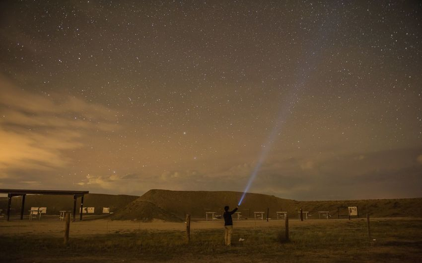 Rear view of man lighting flashlight star field in sky