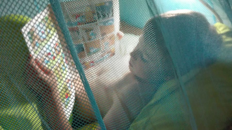 High angle view of boy reading book while lying on bed at home