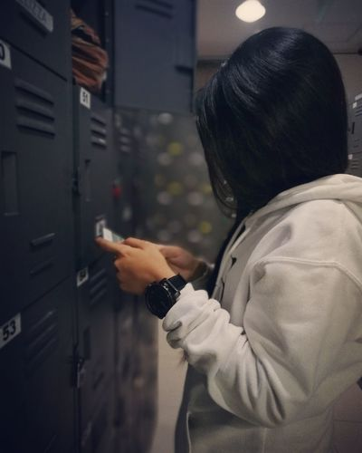 Close-Up Of Woman Using Mobile Phone While Standing By Lockers
