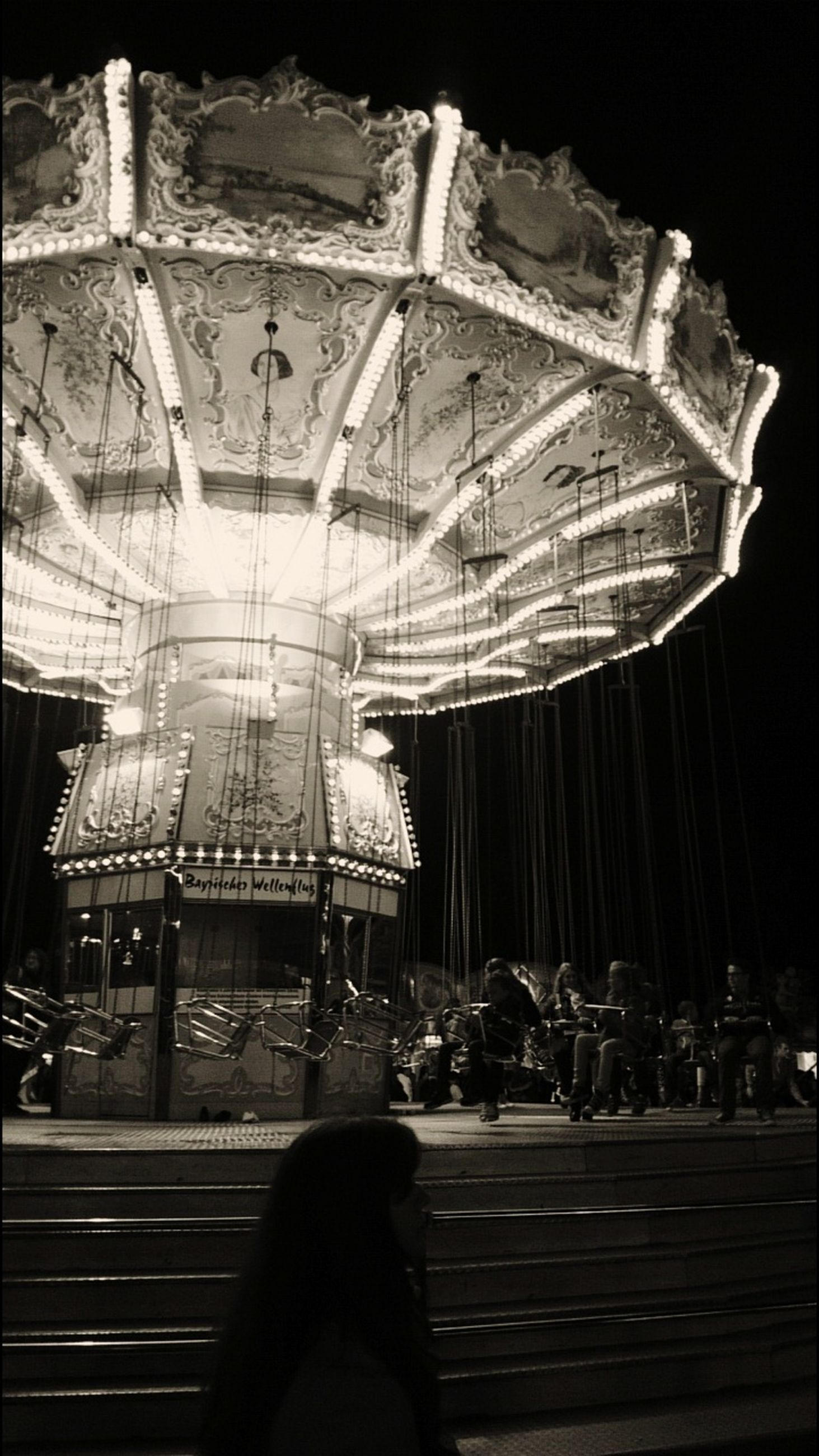 amusement park, amusement park ride, arts culture and entertainment, night, real people, illuminated, leisure activity, lifestyles, people, women, group of people, low section, sitting, architecture, carousel, incidental people, crowd, seat, human leg, stage