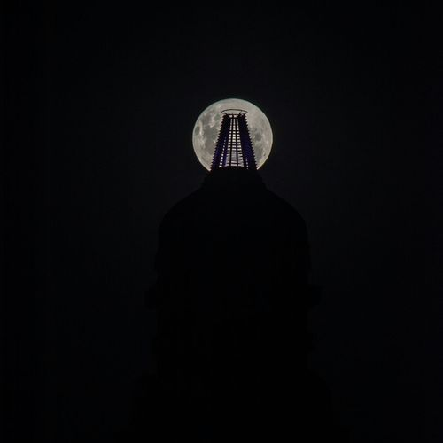 Rear view of silhouette man standing against black background