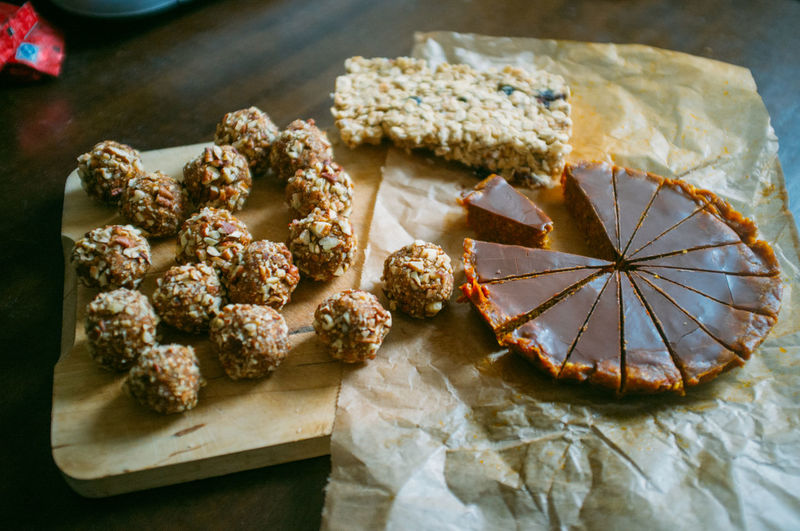 High Angle View Of Almond Balls And Chocolate Tart With Nut Bar On Cutting Board