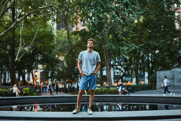 Young man standing on road in city