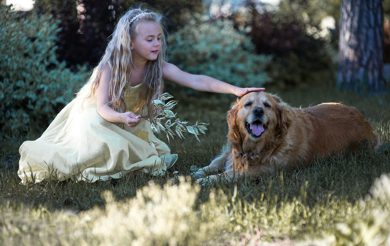 Girl with dog sitting on grass