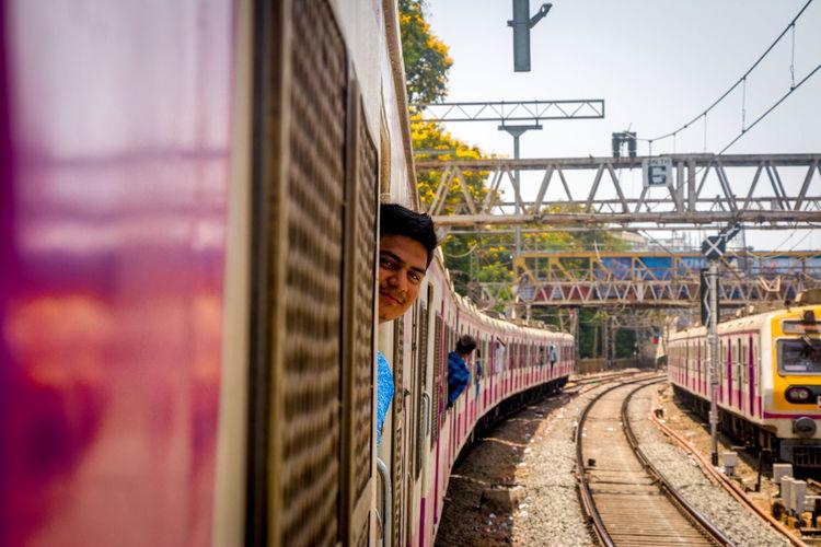 Portrait Of Man Peeking From Train Door In City