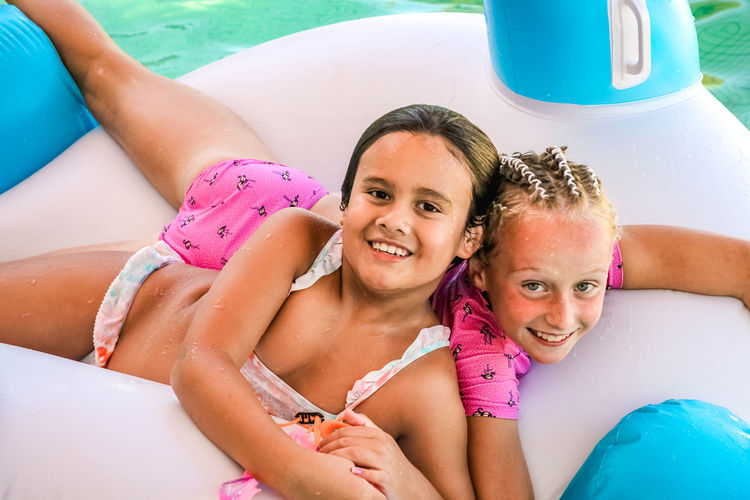 friendship and fun summer in the pool, childhood, girls, play, inflatables Portrait Smiling Looking At Camera Childhood Togetherness Two People Happiness Females Pool Emotion Leisure Activity Child Swimming Pool Real People Bonding Girls Lifestyles Day Inflatable  Positive Emotion Outdoors Diversity Vacations
