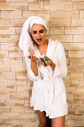 Woman Wearing Bathrobe Looking At Face Cream While Standing Against Wall