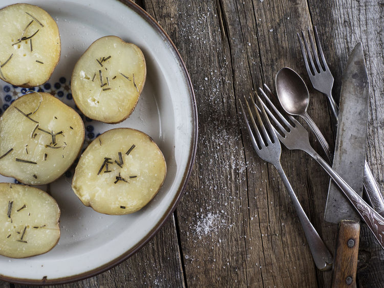 Baked potatoes with rosemary on plate and cutlery on an old weathered wooden table Baked Close-up Cuttery Directly Above Eating Utensil Fork Freshness High Angle View Indoors  Knife No People Old Buildings Plate Potatoes Ready-to-eat Rosemary Spoon Star Anise Table Weathered Wooden