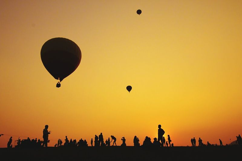 Low Angle View Of Hot Air Balloons Flying Over Landscape