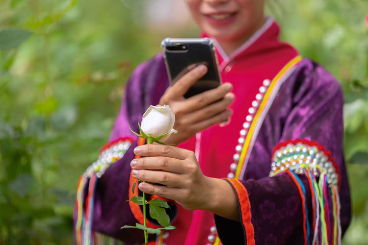 Holding Technology Wireless Technology Mobile Phone Smart Phone Real People One Person Communication Portable Information Device Leisure Activity Using Phone Connection Women Lifestyles Photography Themes Telephone Smiling Front View Day Focus On Foreground Outdoors