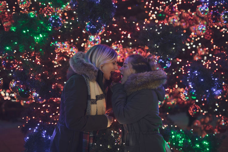 Female friends eating caramelized apple during christmas at night