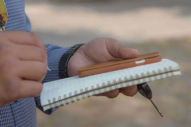 Midsection Of Man With Smart Phone Writing In Diary While Standing Outdoors