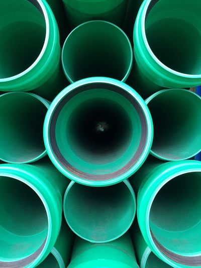 Full Frame Shot Of Stacked Green Pipes