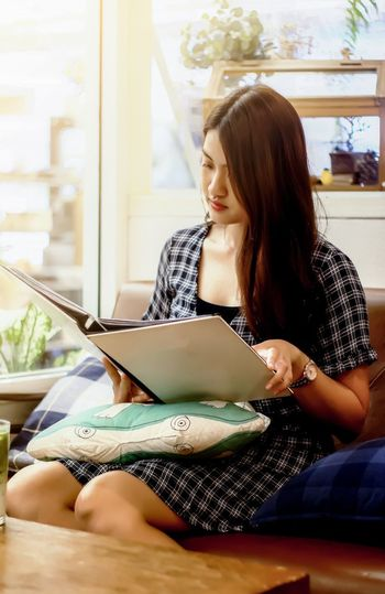 Beautiful young woman using smart phone at home