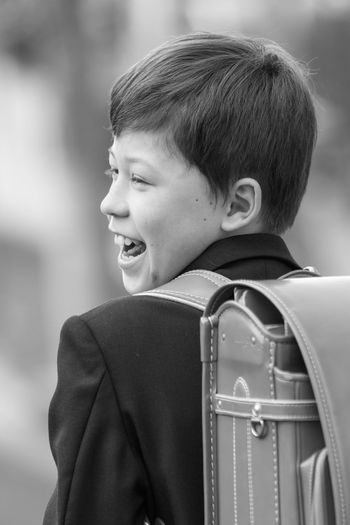 Rear view of cheerful male student looking away