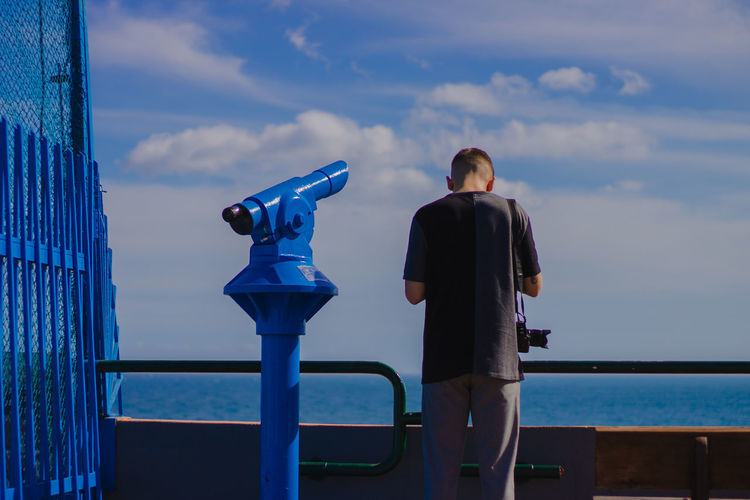 Rear View Of Man Standing By Coin-Operated Binoculars At Railing Against Sea At Observation Point