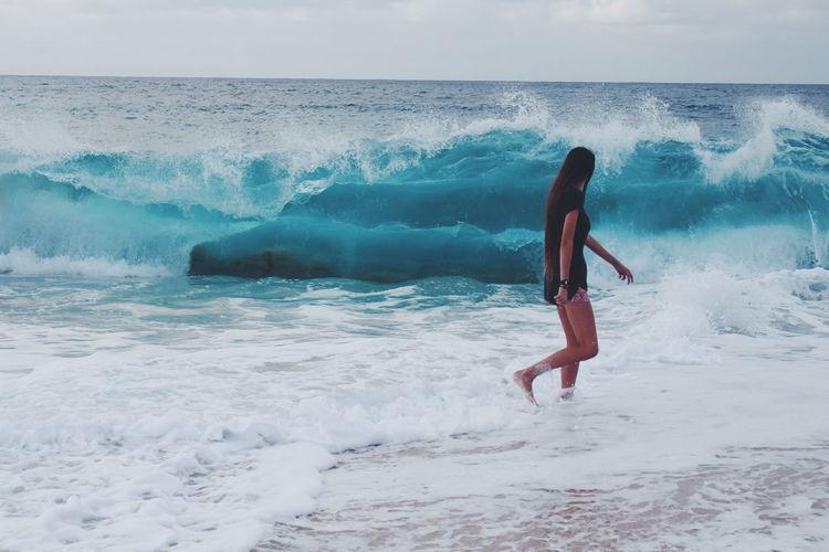 Sea waves rushing towards woman walking on shore