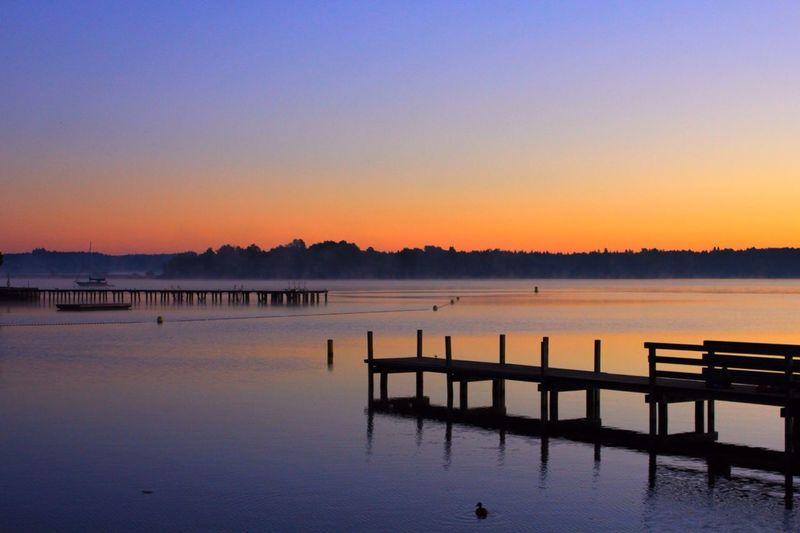Pier on lake at sunset