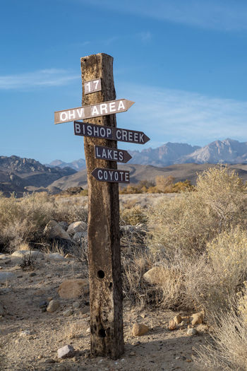 Wooden road sign with wood arrows in desert mountain landscape