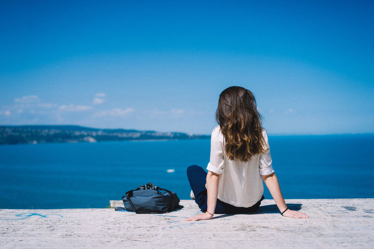 Explore Backpack Bag Beauty In Nature Blue Casual Clothing Horizon Over Water Lifestyles Nature One Person Outdoors Real People Sea Sitting Sky Sunlight Travel Water Women Young Women