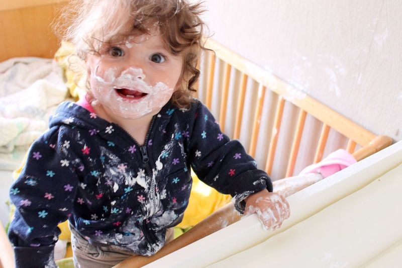 Portrait of cute girl with face paint in crib