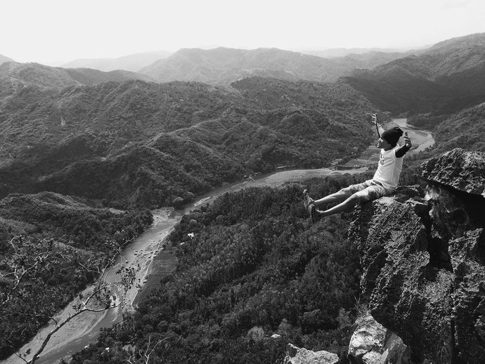 Young man with arms outstretched sitting on cliff