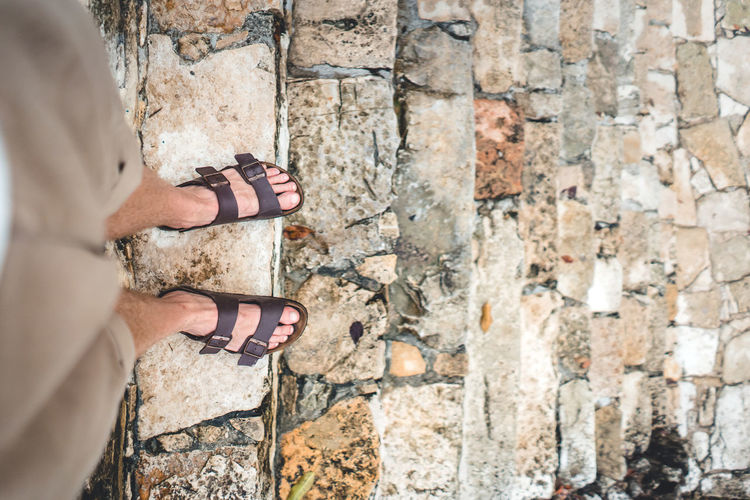 Human Body Part One Person Body Part Wall Lifestyles Solid Adult Standing Low Section Leisure Activity Architecture Day Wall - Building Feature Women Stone Wall Built Structure Real People Shoe Outdoors Nail Human Foot Human Limb