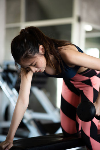 Young Woman Lifting Dumbbell At Gym