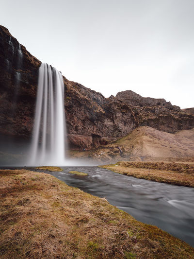 scenic view of the Seljalandsfoss waterfall in Iceland against sky Adventures Hvolsvöllur Iceland Iceland Memories Nature Photography Rangárþing Eystra SeljalandsfossWaterfall Sightseeing Water Energy Winter Beauty In Nature Blurred Motion Day Environment Flowing Flowing Water Formation Iceland Trip Long Exposure Motion Mountain Nature No People Non-urban Scene Outdoor Photography Outdoors Philipp Dase Power In Nature Rock Rock - Object Scenics - Nature Seljalandsfoss Sky Solid Tranquil Scene Travel Destination Water Water Element Water Environment Water Power Waterfall