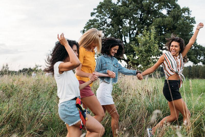 Full length of happy friends enjoying on field