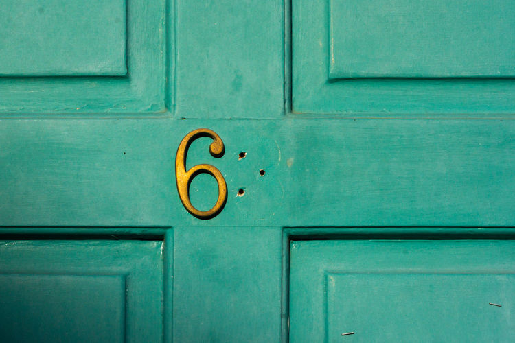 House number sixty something with missing second digit on a turquoise wooden front door in london
