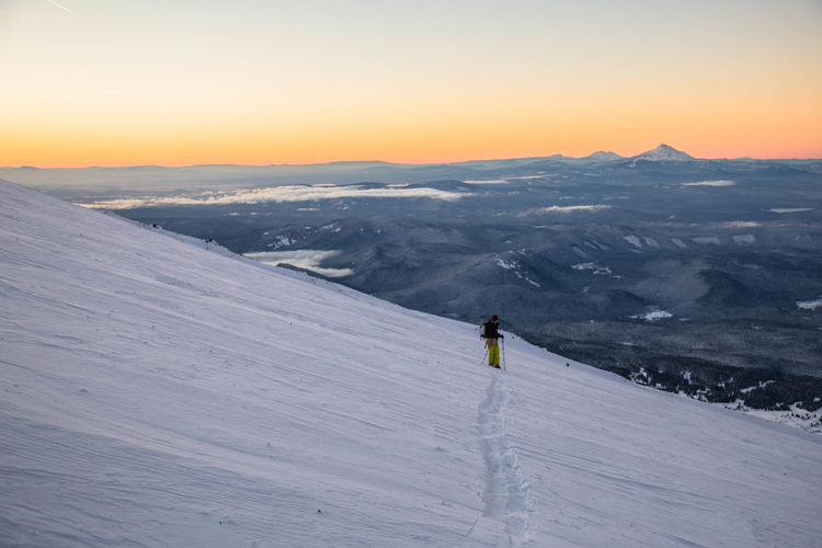 Man Skiing On Snowcapped Mountain During Sunset