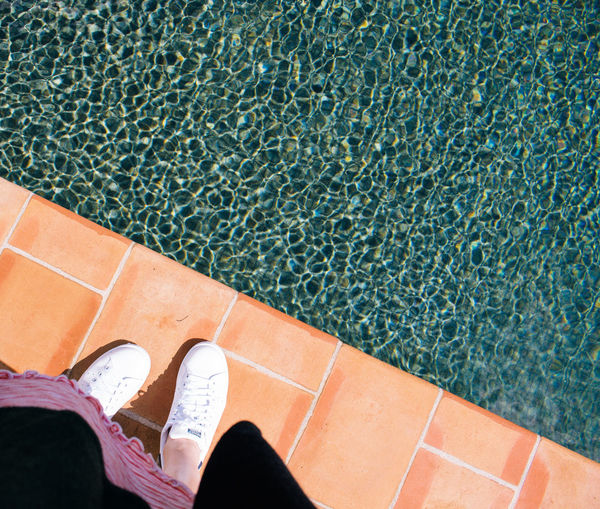 Low Section Of Woman Standing In Front Of Swimming Pool