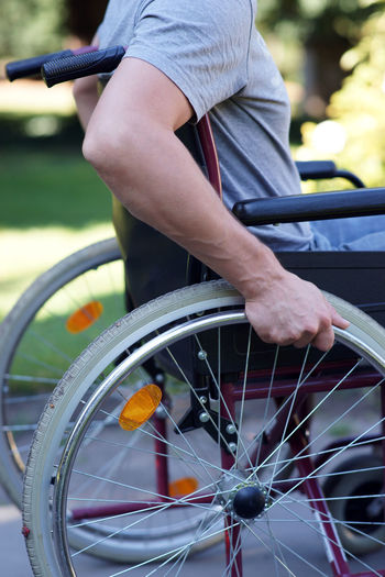 Midsection of man sitting on wheelchair