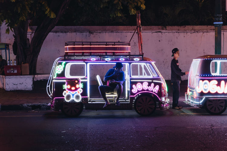 Adult Car City Group Of People Illuminated Land Vehicle Lifestyles Men Mode Of Transportation Motor Vehicle Night Occupation Outdoors People Real People Road Stationary Street Transportation