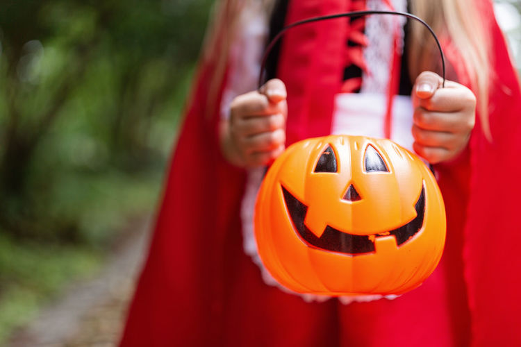 Little girl in costume of red hat in the park. happy halloween concept. high quality photo