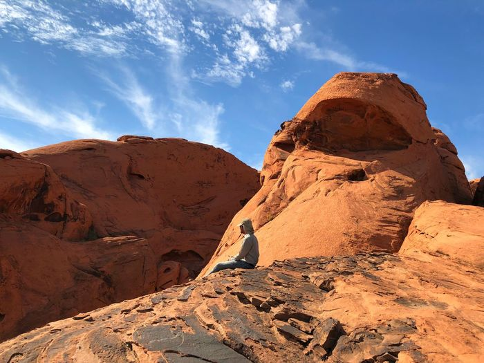 Man sitting on rock formation against sky