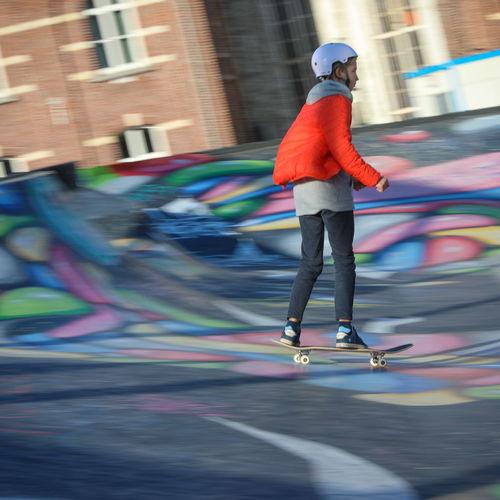 Full length of man skateboarding on skateboard in city