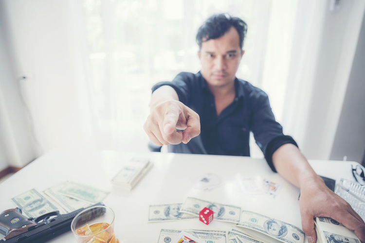 Man sitting with currency at table